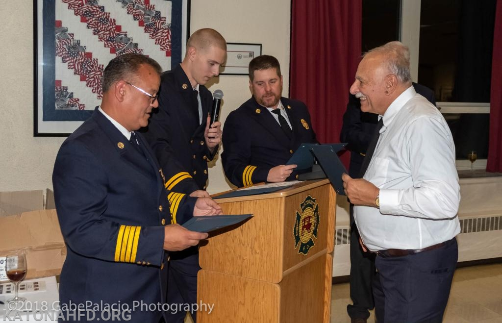 Driver-Operator Emeritus Chris Stanton accepts a 35-year certificate from the Chiefs.