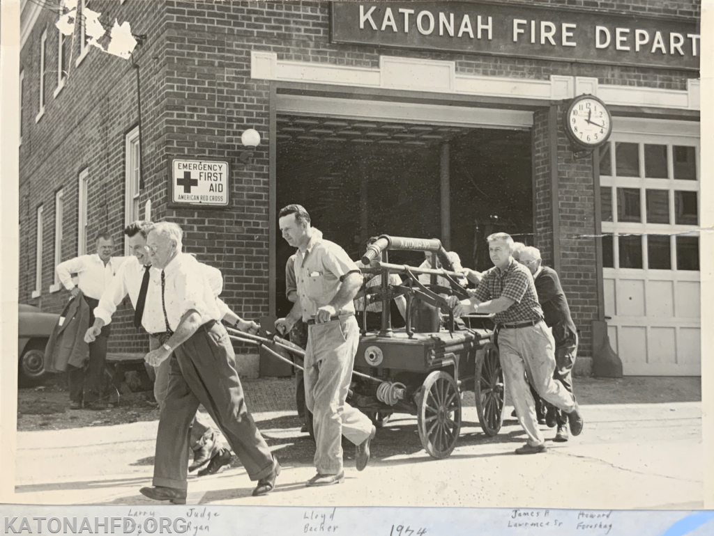 "Chief Lawrence is pictured second from right helping to push the ""Pride of Katonah"" hand pumper--the first piece of fire apparatus purchased by Katonah Fire Department. Pictured in back is what is now known as the ""Old Firehouse Building""--KFD's headquarters prior to moving to 65 Bedford Road."